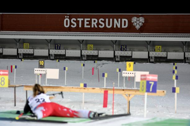 A female Para biathlete laying on the ground to shoot on the target