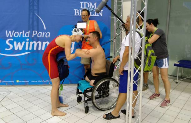 An female swimmer talking to a male swimmer in a wheelchair with four people in the background