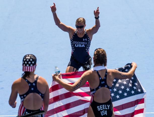Two women holding the US flag waiting for their teammate to cross the finish line