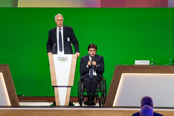 A man standing and another man in a wheelchair on stage