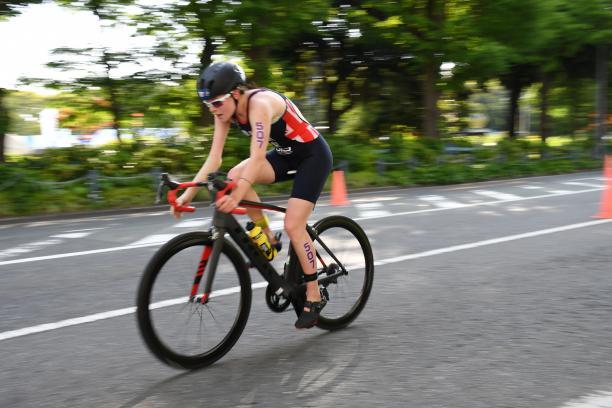 Female British triathlete with arm impairment rides her bike