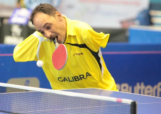 Egyptian male table tennis player holds racket in mouth and attempts to hit the ball