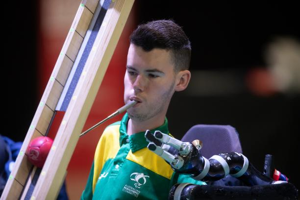 Australian male boccia player holds device in mouth to push ball down ramp