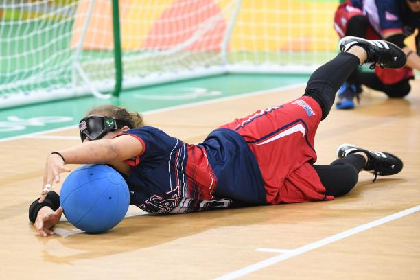 a female goalball player saves a shot