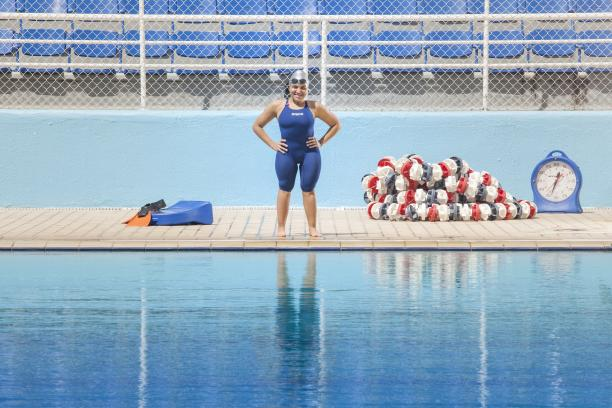 A short stature woman standing in front of a swimming pool