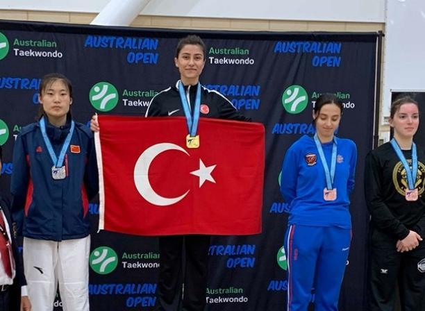 Woman taekwondo fighter on the podium holding the Turkey flag