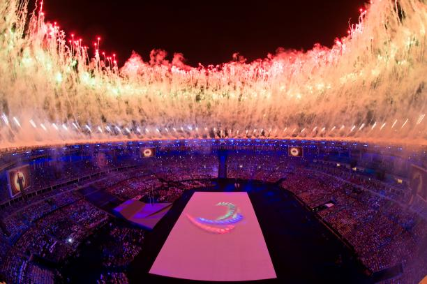 a high shot of the Olympic Stadium in Rio with fireworks going off and the Agitos symbol on the floor