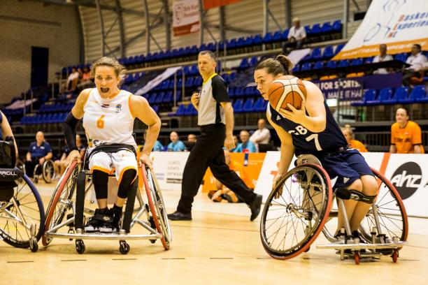 British female wheelchair basketball player makes a move with the ball while a Dutch player turns to defend her