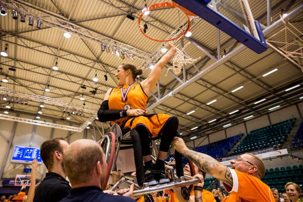 Dutch female being lifted up on her wheelchair to the basketball hoop