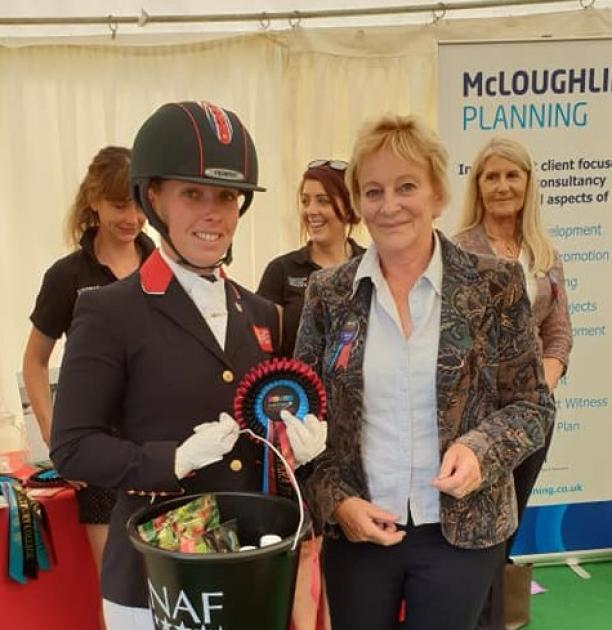 British female dressage athlete holds bucket of prize with an organiser