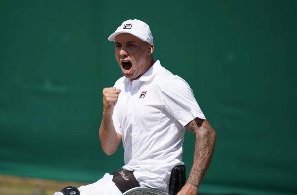 British male wheelchair tennis player clutches fist to celebrate a point