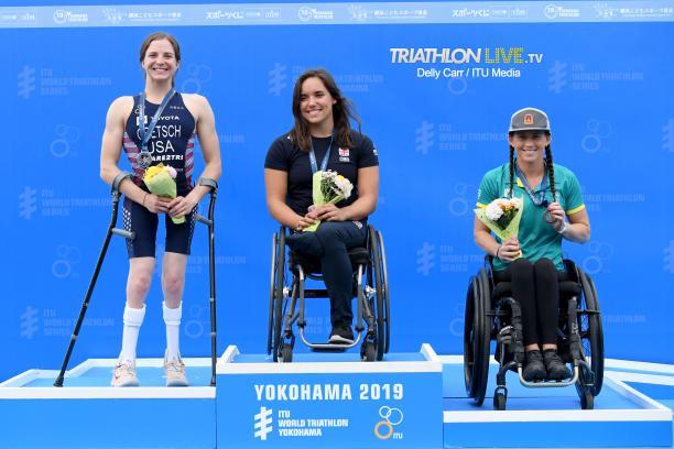 Three female triathletes on a podium smiling