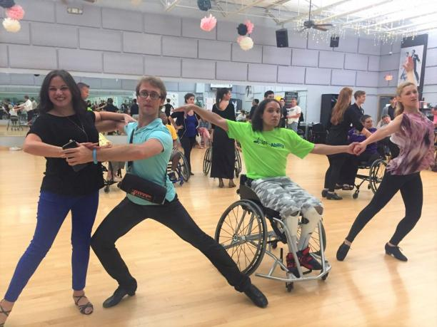 Two pairs of Para dance couples pose in a dance studio