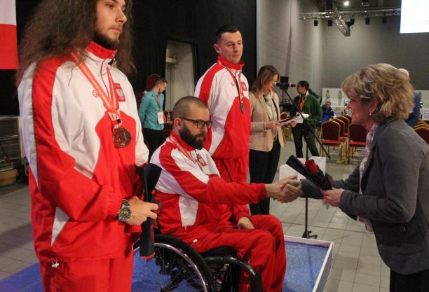 Man in wheelchair shakes hand with woman during medal ceremony