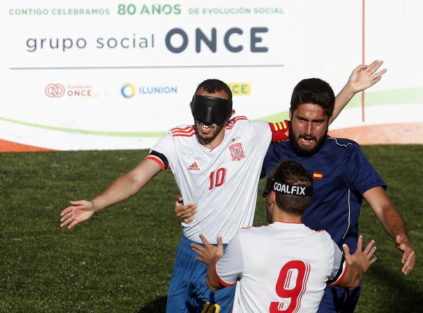 three male blind footballers including two from Spain battle for the ball