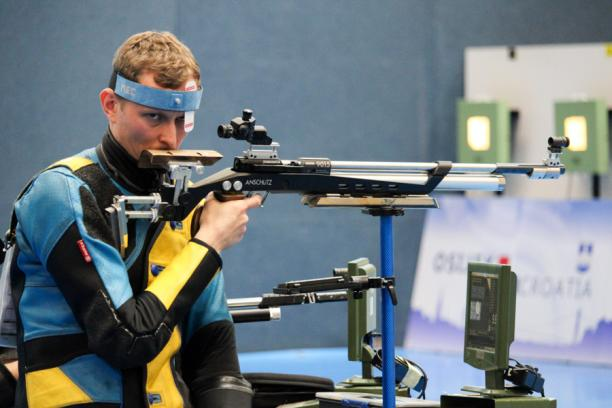 A man with a rifle in a sitting position at a shooting range