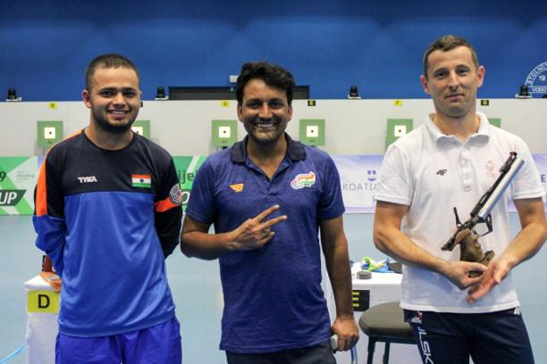 Three male pistol shooters pose for a photo