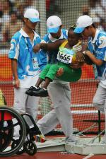 Jamaican athlete being transferred to her wheelchair during the 2008 Beijing Games