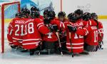 The Canadian Ice Sledge Hockey Team gathered around the goal.