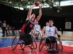 A picture of a man in a wheelchair shooting a ball in a Wheelchair Basketball match