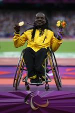 A picture of a man in a wheelchair showing his gold medal