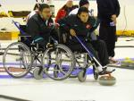 A picture of a man in wheelchair playing curling