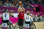 A picture of a woman in a wheelchair shooting between two defenders during a wheelchair basketball match.