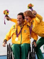 A picture of a man in a wheelchair and woman celebrating their victory with a gold medal around their necks