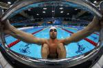A picure of a man in the pool holding starting block with his hands
