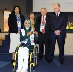 'Iranian archer Zahra Nemati seated in a wheelchair holding an award surrounded by people' logo