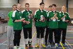 A goalball team faces the camera with their tournament trophy.