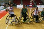 Three wheelchair basketball players fight for the ball