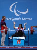 Fatma Omar raises her hands in celebration after winning her 4th consecutive Paralympic gold.