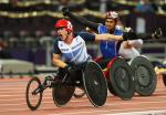 A picture of men in a wheelchair racing on a track