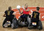 A picture of three wheelchair rugby players in action.