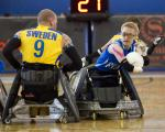 A picture of 3 person in a wheelchair with of those person having a ball in his hand.