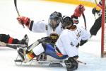 A picture of 2 men in sledges celebrating a goal during a ice sledge hockey match