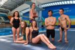Group shot of swimmers in front of a pool