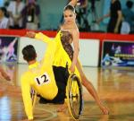 Man in wheelchair and woman standing pose while dancing