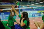 Girls and man doing high five, sitting on a volleyball field of play