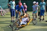 Kid in a handbike with other people standing around and watching