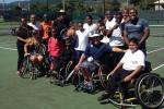 Group picture of people in wheelchairs and standing on a tennis court