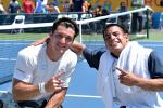 two tennis players smiling to the camera and pointing their index finger making a number 1 sign
