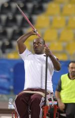 Man sitting, throwing a javelin