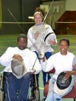 Two fencers in a wheelchair holding a sword and an instructor standing in the background.