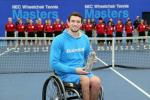 Man in wheelchair on a tennis court, showing a trophy to the camera