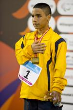 Man in yellow training suit on a podium.