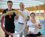 Two men and a woman in a wheelchair pose in front of a swimming pool.