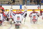 Sledge hockey players on the ice without their helmets, celebrating