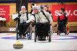 Wheelchair curler on the ice with team in the background
